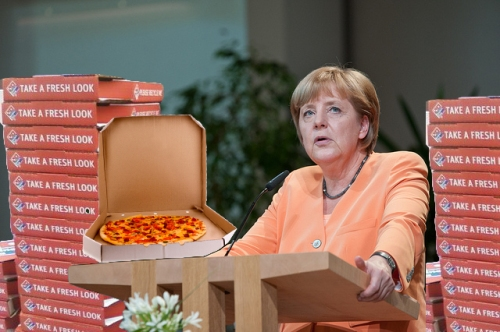 Chancellor Angela Merkel of Germany displays her free pizza – an apology from NSA for monitoring her cell phone.  The NSA also offered to kill one person for her.